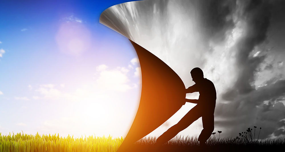 Man turning the page on a black and white, cloudy day to reveal sunny, blue skies