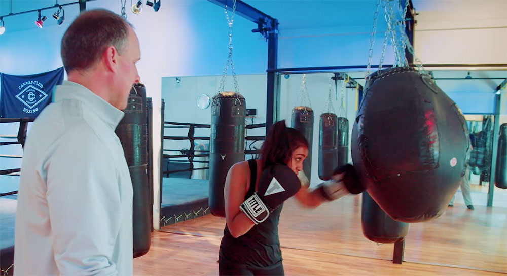 Boxing gym owner looks on as a young woman punches a bag