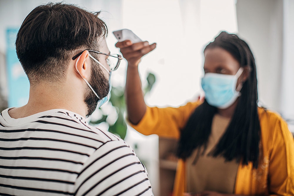 Woman taking man's temperature at a healthcare facility