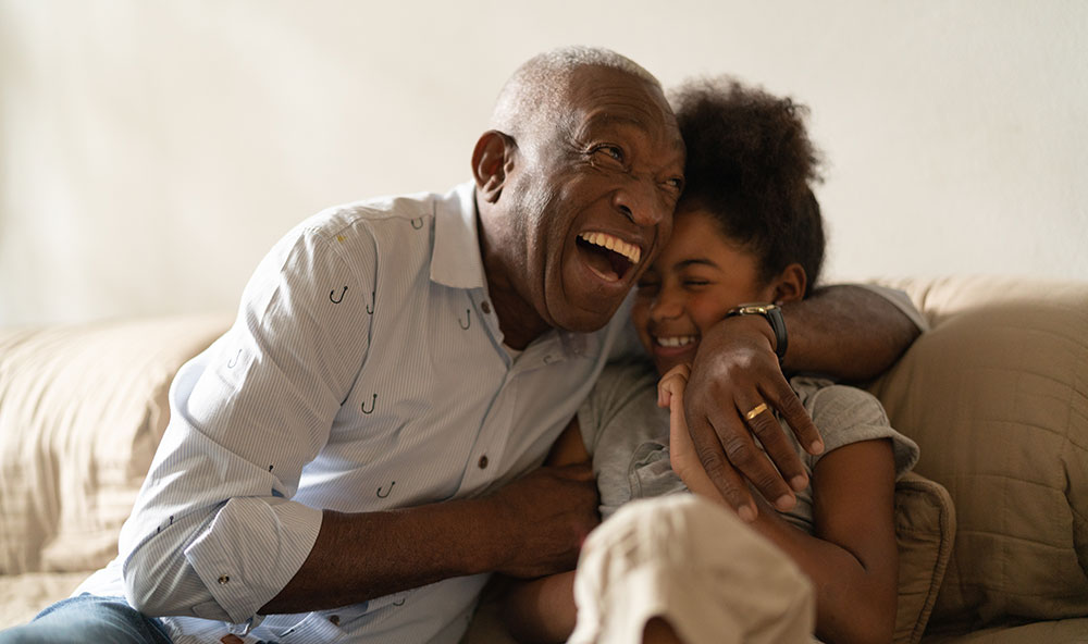 elderly man and young girl embracing and laughing