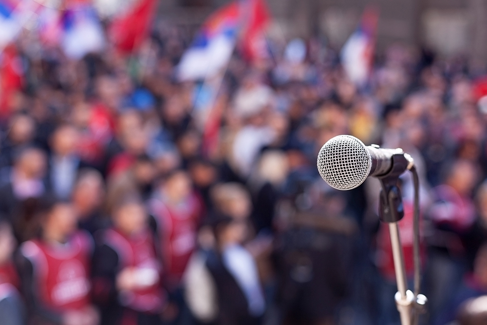 microphone and stand in front of a large group of people