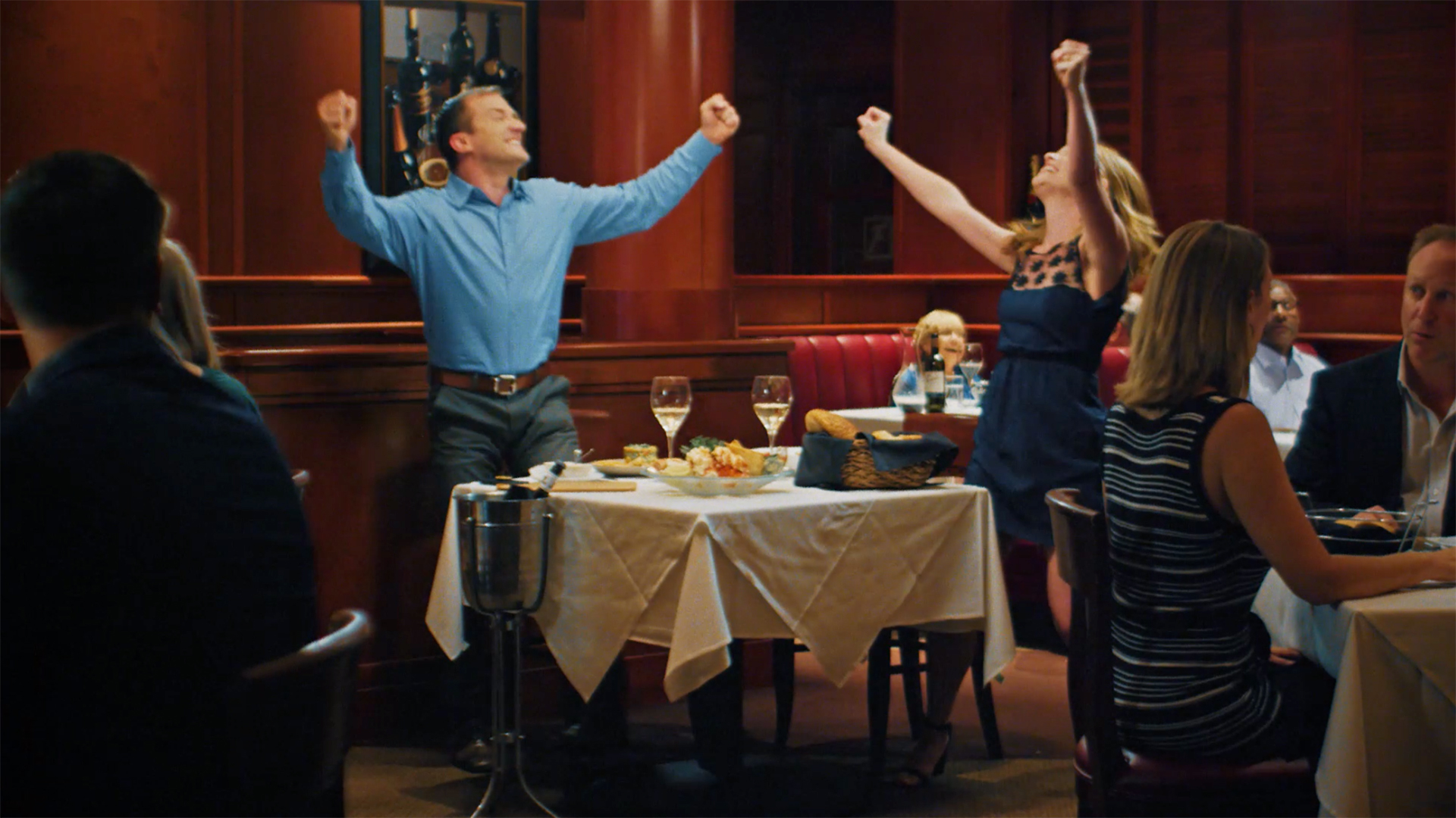 Young couple standing up and celebrating at a fancy restaurant