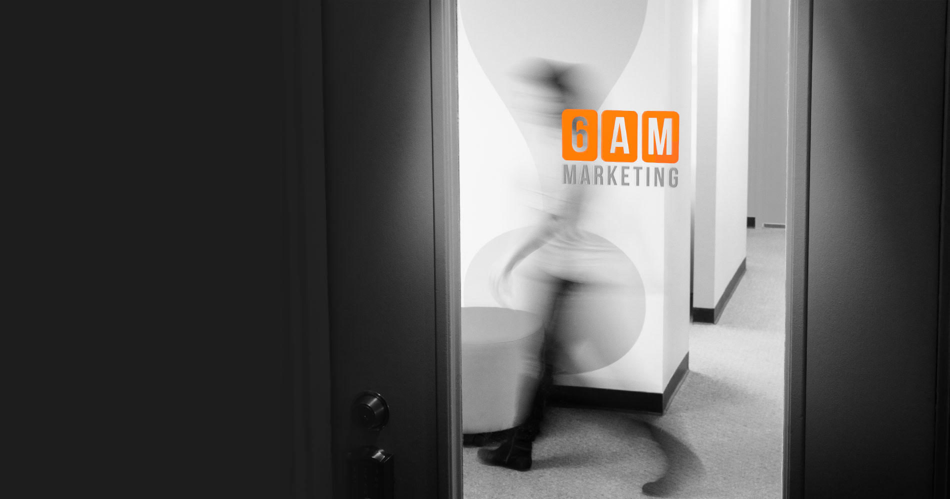 blurred streak of a person walking by as seen through the front door of 6AM Marketing