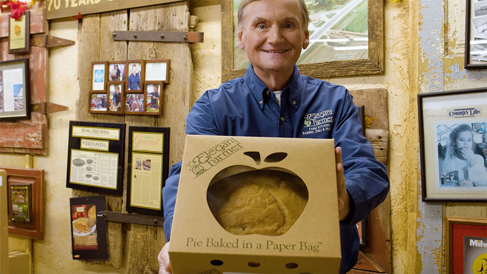 Elegant Farmer owner holding one the company's renowned apple pies