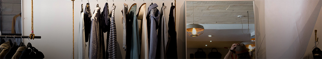 several items of men's clothes hanging on a rack in a store