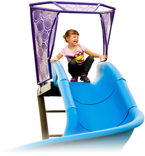 young girl smiling at the top of a playground slide