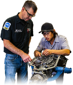 professor overseeing a student working on an engine