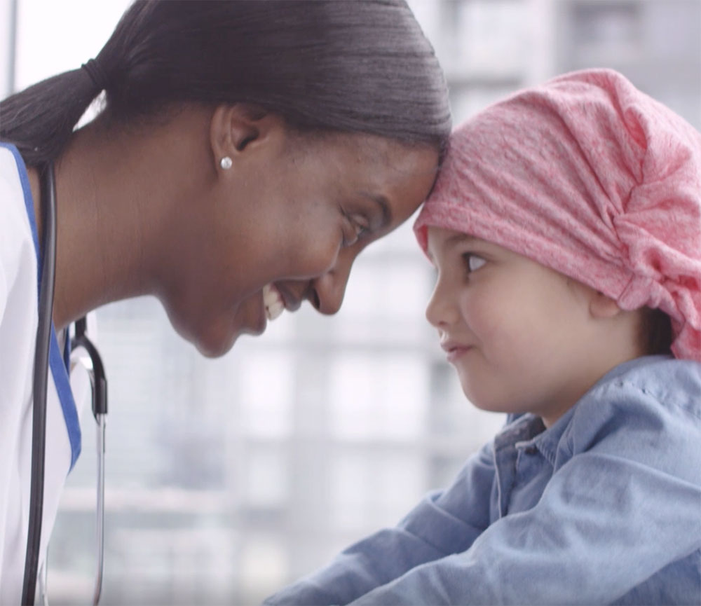 Female nurse and young girl, heads pressed together and looking at each other; healthcare video marketing