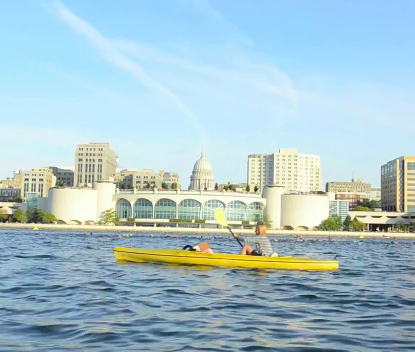 Woman rowing on Lake Monona in Madison, Wisconsin, with the state capitol in the background